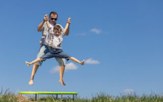 Father and son jumping on trampoline after chiropractic care